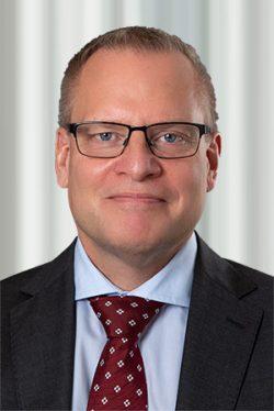 Man med glasögon och röd slips som tittar in i kameran